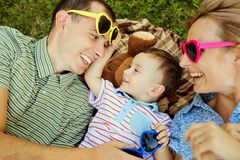 Happy family in the park on the grass. Mother and father kissing hugging their son lying on grass in nature in summer stock photos