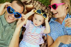 Happy family in the park on the grass. Mother and father kissing hugging their son lying on grass in nature in summer stock image