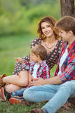 Happy family in a park on grass Stock Photos