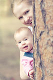 Happy family in the park. Mom and toddler peeking from behind a. Happy family in the park for a walk. Mom and toddler peeking from behind a tree royalty free stock image