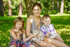 Happy family in the park. Mother, daughter and son are sitting o. N the grass. Woman, girl and boy playing with a cat outdoors Stock Photography