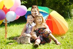 Happy family in the park. Mother, daughter and son are sitting o. N the grass. Woman, girl and boy playing with a cat outdoors with a colorful umbrella and Royalty Free Stock Photos