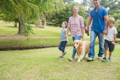 Happy family in the park with their dog Royalty Free Stock Photography