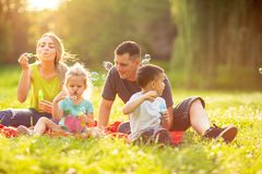 Happy family in the park together on a sunny day - children blow. Happy family in the park together on a sunny day – cute children blow soap bubbles royalty free stock photography