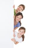 Happy family peeking from blank billboard Stock Image