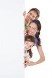 Happy family peeking from blank billboard. Portrait of happy family peeking from blank billboard over white background Royalty Free Stock Photo
