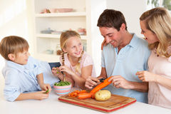 Happy Family Peeling Vegetables In Kitchen Stock Image
