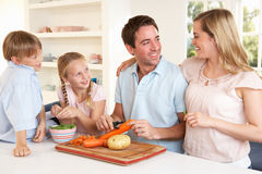 Happy family peeling vegetables in kitchen Royalty Free Stock Images