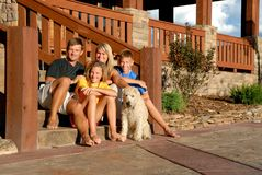 Happy family and pet. A picture of a happy family, sitting together on the steps outside their home with their pet dog Stock Images