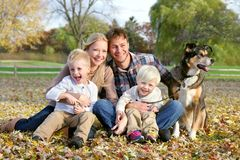 Happy Family and Pet Dog Autumn Portrait. A happy family of four people, including mother, father, young child, and toddler brother are sitting outside in the Stock Photo