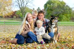 Happy Family and Pet Dog Autumn Portrait. A happy family of four people, including mother, father, young child, and toddler brother are sitting outside in the Stock Image