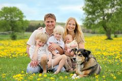 Happy Family and Pet Dog in Flower Meadow. A portrait of a happy family of five caucasian people, including big brother, toddler boy, and baby sister are Royalty Free Stock Images