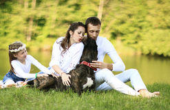 Happy family with pet dog at picnic in a Sunny summer day. pregn Royalty Free Stock Photos