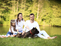 Happy family with pet dog at picnic in a Sunny summer day. pregn Stock Photos