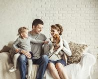 Portrait of a happy family and a pet sitting on a sofa. Happy family and a pet sitting on a sofa in the spacious living room royalty free stock image