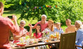 Happy family photographing at dinner in garden stock image