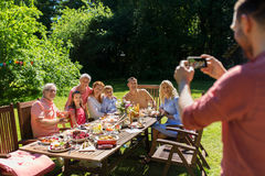 Happy family photographing by smartphone in summer Royalty Free Stock Images