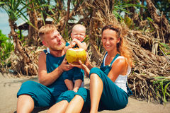 Happy family picnic on beach. Mother, father feed baby boy. royalty free stock photos
