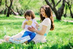 Happy family on picnic for mothers day. Mom and toddler son eating sweets outdoor in spring or summer. Park royalty free stock image