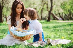 Happy family on picnic for mothers day. Mom and toddler son eating sweets outdoor in spring. Or summer park royalty free stock photography