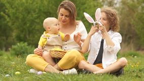 Happy family on a picnic in the park. The kid is considering an Easter bunny costume. Easter family, two brothers and stock footage