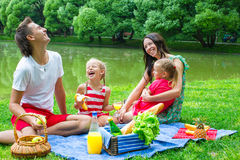 Happy family picnicking in the park and have fun Stock Image