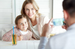 Happy family picturing by smartphone at restaurant Stock Image