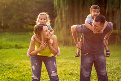 Happy family - Family piggyback their children and have fun together in park stock images