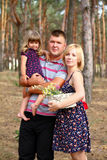 Happy family in a pine forest with a basket of daisies Stock Photography