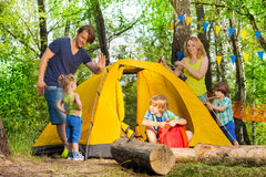 Happy family pitching up a tent in the forest royalty free stock photography