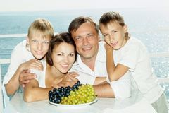 Happy family with a plate of grapes Stock Photography