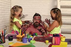Happy family play. Daughters and dad with painted hands. Body art and painting. Girls drawing on men face skin with colorful paints. Fathers day and family Royalty Free Stock Photos