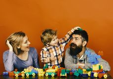 Happy family play. Family with cheerful faces build out of colored construction blocks Royalty Free Stock Photography