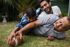 Happy family playing american football in yard Stock Images
