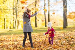 Happy family playing with autumn leaves at park Stock Image