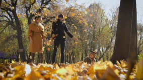 Happy family playing with autumn leaves in park. Mom and dad throw leas up in the air. Small child look at them and stock video