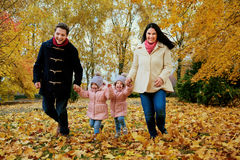 Happy family playing in autumn park. Royalty Free Stock Photography
