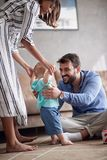 Happy family playing and baby learning to walk at home. Happy family playing and baby boy learning to walk at home stock photography