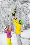 Happy family during the winter vacations. Happy family playing with baby boy standing in winter spots clothes outdoors during the winter vacations stock photos