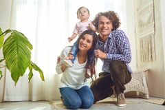 Happy family playing with baby at home. Mother, father and daughter play together in a room stock image