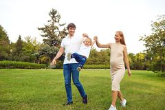 Happy family playing with baby in the park. Happy family playing with baby in the park in spring summer royalty free stock images