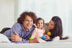 Happy family playing with the baby in the room. Young mother and. Father play with the daughter on a bed indoors royalty free stock photography