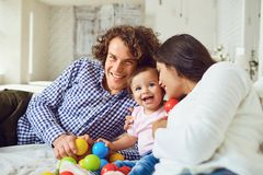 Happy family playing with the baby in the room. Young mother and. Father play with the daughter on a bed indoors stock image