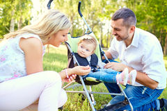 Happy family playing with a baby in a stroller in the park. Happy family playing with a baby in a stroller in the park autumn summer stock photography