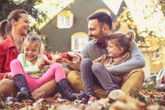 Happy family playing at backyard, autumn season. Smiling young family royalty free stock image