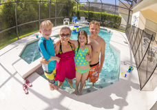 Happy Family playing in a backyard swimming pool. Fisheye photo of a beautiful young family playing together in a covered backyard pool outdoors Stock Photography