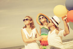 Happy family playing  with balloons on the beach at the day time Stock Photos