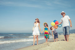 Happy family playing  with balloons on the beach at the day time Royalty Free Stock Photos