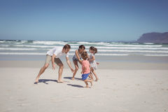 Happy family playing at beach Stock Image