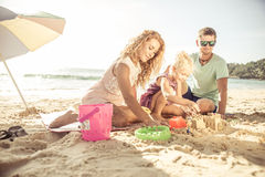 Happy family playing on the beach. And build some sand castle stock photography